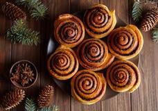 桂皮卷小圆面包在一张木早餐桌上的圣诞节烘烤 顶视图 与杉木锥体的欢乐装饰 免版税库存图片
