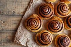 桂皮卷小圆面包在一张木早餐桌和羊皮纸上的圣诞节烘烤 顶视图 免版税图库摄影