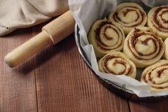 桂皮卷 新近地被烘烤的桂香小圆面包用填装在羊皮纸的香料和可可粉 顶视图 甜自创酥皮点心 免版税库存图片