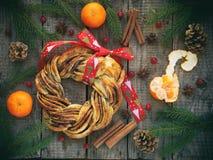 桂香可可粉红糖花圈小圆面包 甜自创圣诞节烘烤 滚动面包,蜜桔,在木背景的装饰 免版税库存图片