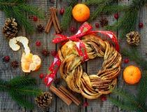 桂香可可粉红糖花圈小圆面包 甜自创圣诞节烘烤 滚动面包,蜜桔,在木背景的装饰 库存照片