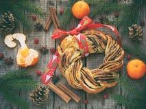 桂香可可粉红糖花圈小圆面包 甜自创圣诞节烘烤 滚动面包,蜜桔,在木背景的装饰 免版税库存照片