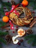 桂香可可粉红糖花圈小圆面包 甜自创圣诞节烘烤 滚动面包,蜜桔,在木背景的装饰 图库摄影