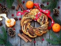 桂香可可粉红糖花圈小圆面包 甜自创圣诞节烘烤 滚动面包,蜜桔,在木背景的装饰 库存图片