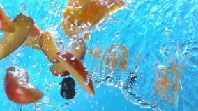 桃子切飞溅入水的橙色黑醋栗苹果倾吐下来在慢动作的果子射击了在1500 fps 股票视频