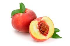 桃子和一半与在白色背景隔绝的一片绿色叶子 免版税库存照片