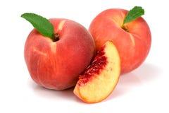 桃子和切片与在白色背景隔绝的一片绿色叶子 免版税库存照片