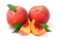 桃子和切片与在白色背景隔绝的一片绿色叶子 库存照片