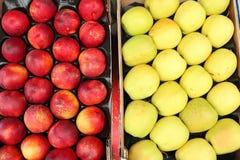 桃子和黄色苹果在卖市场的篮子 免版税库存照片
