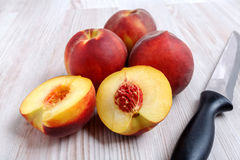 桃子和黑刀子在桌上 免版税库存照片