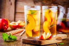 桃子在一块玻璃的冰茶用薄菏 库存图片