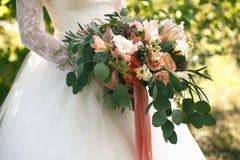 桃子树荫婚姻的柔和的被弄乱的花束与桃红色丝带的 库存照片