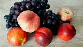 桃子油桃和黑暗的葡萄收获  库存图片