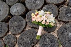 桃子玫瑰和白色兰花韦德花束在树桩 免版税库存照片