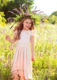 桃子礼服的女孩,有野花花圈的  免版税库存图片