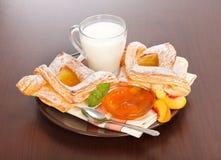 桃子蛋糕和果酱用牛奶早餐 免版税库存图片