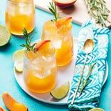 桃子鸡尾酒、嘶嘶响、冰茶用新鲜的迷迭香和石灰 背景看板卡祝贺邀请 免版税图库摄影