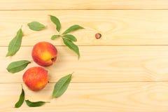 桃子 与绿色叶子的果子在木桌上 与拷贝空间的顶视图 库存照片
