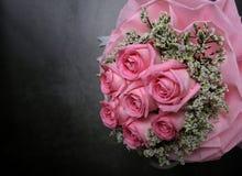 桃红色上升了在黑水泥背景的花束 免版税库存照片