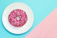 桃红色上釉圆环一张顶上的照片与白色的在蓝色和桃红色背景洒 顶视图 简单派,颜色对比 图库摄影