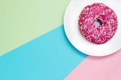 桃红色上釉圆环一张顶上的照片与白色的在蓝色,绿色,桃红色背景洒 顶视图 简单派,颜色对比 免版税库存照片