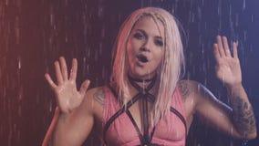 桃红色上面和配刀腰带的性感的可爱的女孩在雨中呼喊并且唱歌 痛苦 无报答的爱 音乐夹子 股票录像