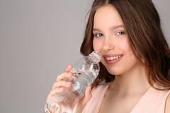 桃红色上面的夫人与瓶水 关闭 灰色背景 免版税库存图片