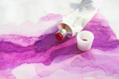 桃红色丙烯酸漆管和手拉的抽象洋红色水彩图画图片在白色织地不很细纸背景 免版税图库摄影