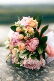 从桃红色中介子和玫瑰的新娘花束 免版税库存照片