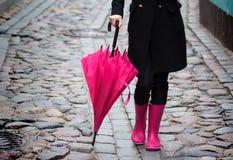 桃红色伞和桃红色胶靴 免版税库存图片