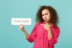 桃红色便服的非洲女孩指向在文本板讽刺的食指隔绝在蓝色绿松石墙壁上 库存照片