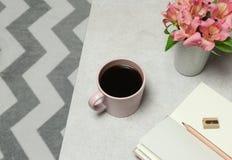 桃红色便条纸,铅笔,咖啡杯,在灰色石桌安置的花 免版税库存图片