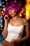 桃红色假发的妇女在夜街道上 免版税库存照片