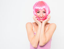 桃红色假发的快乐的少妇和摆在白色背景 免版税图库摄影