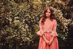 桃红色公主的微笑的卷曲儿童女孩在步行穿戴在夏天森林里 库存照片
