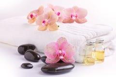 桃红色兰花、润湿的油和温泉石头在白色 免版税库存图片