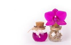 桃红色兰花和两个玻璃瓶在白色背景 温泉概念 装瓶化妆用品 生态自然化妆用品 复制空间 免版税库存照片
