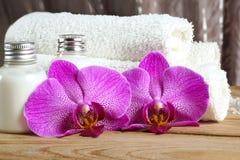 桃红色兰花在毛巾和白色身体化妆水附近开花在温泉治疗屋子 免版税库存照片