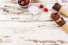 桃红色冰淇凌服务用莓果-草莓和蓝莓在一个黄色碗 奶蛋烘饼锥体用巧克力 轻的土气木头 库存照片