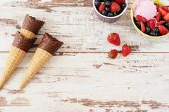 桃红色冰淇凌服务用莓果-草莓和蓝莓在一个黄色碗 奶蛋烘饼锥体用巧克力 轻的土气木头 免版税库存照片