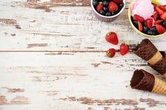 桃红色冰淇凌服务用莓果-草莓和蓝莓在一个黄色碗 奶蛋烘饼锥体用巧克力 轻的土气木头 免版税图库摄影