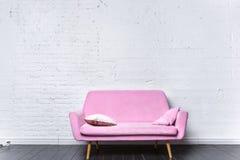 桃红色减速火箭的沙发对白色砖墙 免版税库存照片