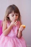 桃红色化装舞会服装的小女孩,吃甜杯形蛋糕 库存图片
