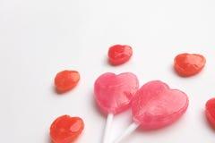 桃红色华伦泰` s天心脏形状棒棒糖用在逗人喜爱的样式的小红色糖果在空的白皮书背景 概念亲吻妇女的爱人 最少的 免版税图库摄影