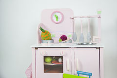桃红色厨房孩子戏弄与器物、食物和一个时钟在w 库存照片