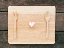 桃红色可爱的心脏蛋白软糖和木匙子有叉子的在木板 免版税库存照片