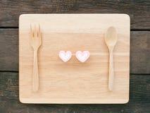 桃红色可爱的心脏蛋白软糖和木匙子有叉子的在木板 免版税库存图片