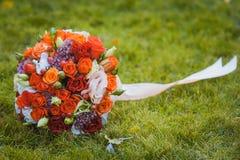桃红色和白玫瑰婚礼花束在草的 免版税图库摄影