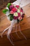 桃红色和白玫瑰新娘花束在木的 库存照片