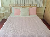 桃红色和白色枕头,在木卧室甜点interi的桃红色毯子 免版税库存图片